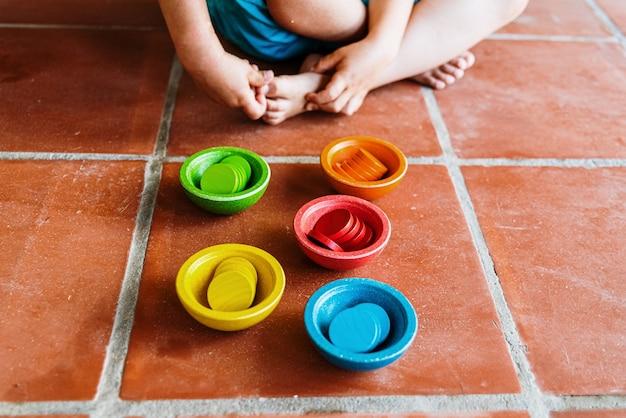 Conjunto de recipientes con forma de cuencos de madera, en varios colores brillantes.
