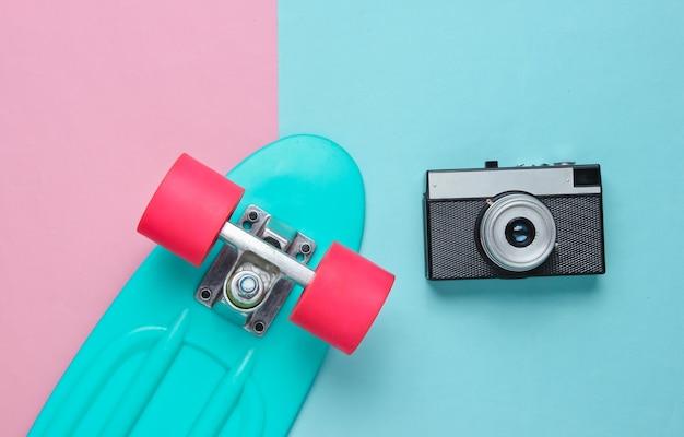 Conjunto retro con monopatín y cámara de película sobre fondo de color pastel. estilo de vida juvenil. vista superior