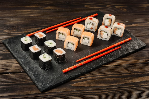 Conjunto de rollos japoneses en un plato de piedra con palillos.