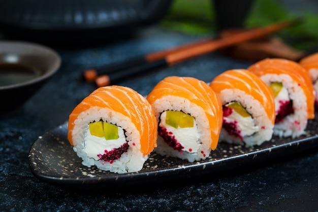 Un conjunto de rollos de sushi filadelfia con pescado rojo y queso crema se encuentra en un bote de placas. rollos de sushi sobre un fondo negro con una tetera de té chino.