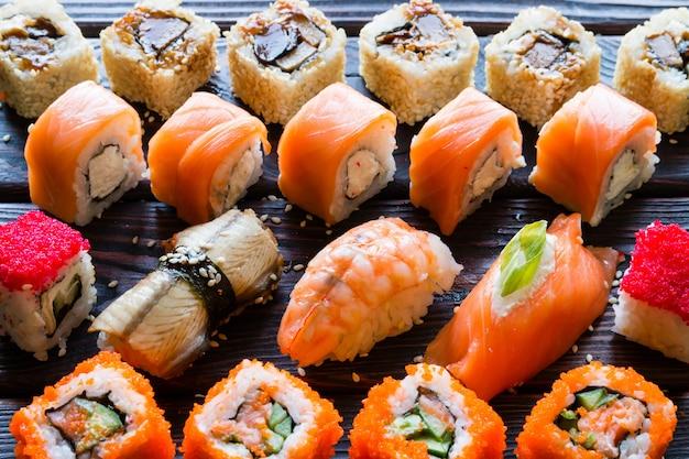 Conjunto de rollos de sushi y nigiri sobre un fondo negro closeup