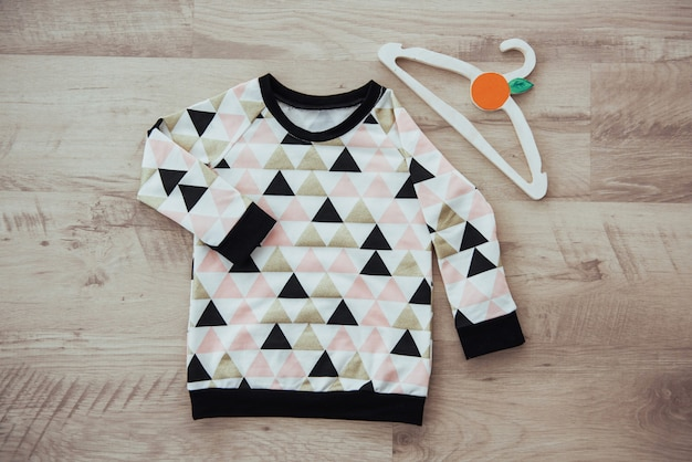 Conjunto de ropa infantil, aislado sobre fondo de madera