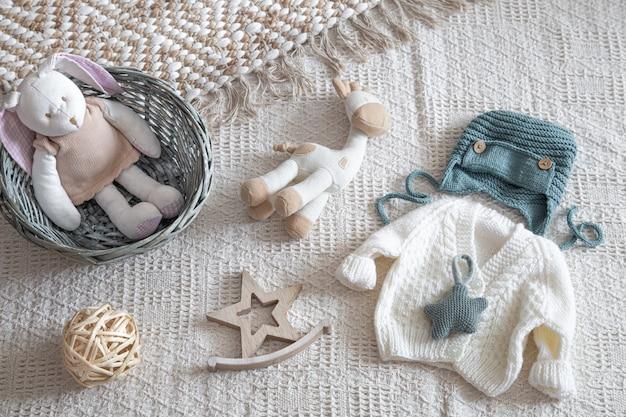 Conjunto de ropa de punto hecha a mano con estilo para niños con varios accesorios en estilo boho, vista superior.