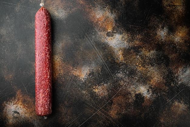 Conjunto de salchicha de salami, sobre fondo rústico oscuro antiguo, vista superior plana, con espacio para copiar texto