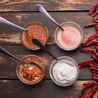 Conjunto de salsas en cuencos con cucharas cerca de chili