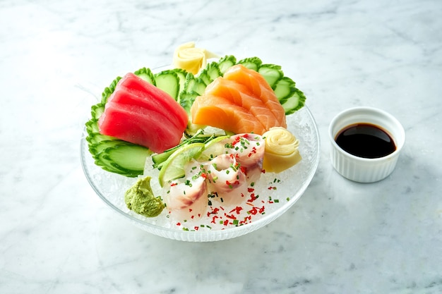 Conjunto de sashimi japonés clásico de salmón crudo, anguila y atún con limón, pepino en un plato sobre una mesa de mármol. de cerca, enfoque selectivo