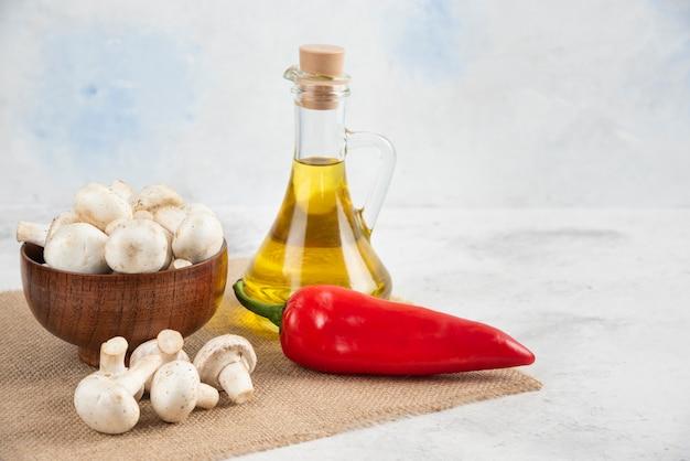 Conjunto de setas blancas, guindillas y aceite de oliva virgen extra sobre el mármol.