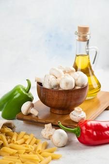 Conjunto de setas blancas, pastas, guindillas y aceite de oliva virgen extra sobre el mármol.
