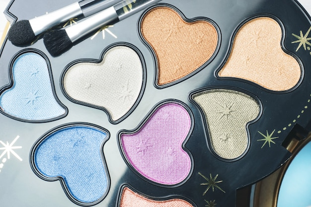 Un conjunto de sombras de ojos de colores y pinceles cosméticos. enfoque selectivo