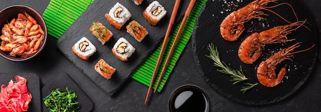 Conjunto de sushi, camarones y maki con una botella de vino en la mesa de piedra. vista superior con espacio de copia.
