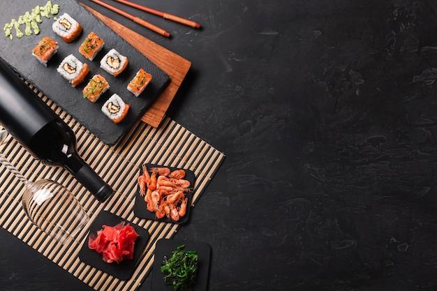 Conjunto de sushi y maki con una botella de vino en la mesa de piedra. vista superior