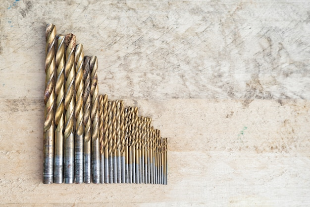 Conjunto de taladros de diferentes tamaños sobre un fondo de madera. vista superior