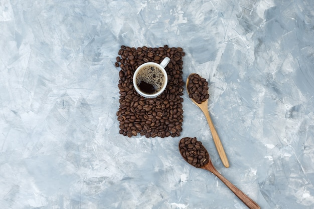 Conjunto de taza de café y granos de café en cucharas de madera sobre un fondo de mármol azul. vista superior.