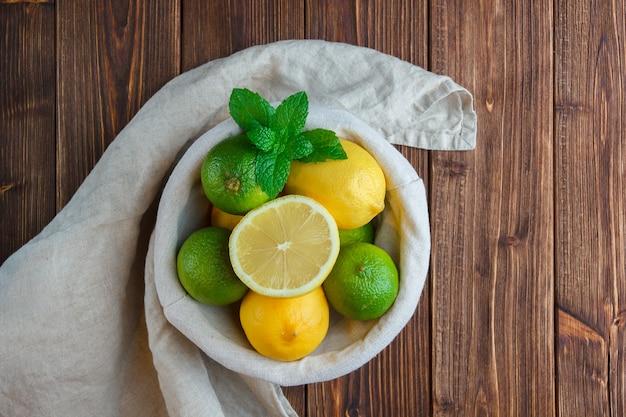 Conjunto de tela blanca, la mitad de limón y limones en una canasta sobre una superficie de madera. vista superior.