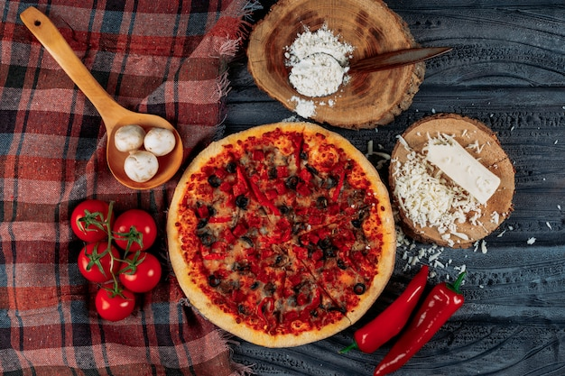Conjunto de tomates, pimientos, champiñones, queso y harina y pizza sobre un fondo de tela de madera oscura y picnic. aplanada