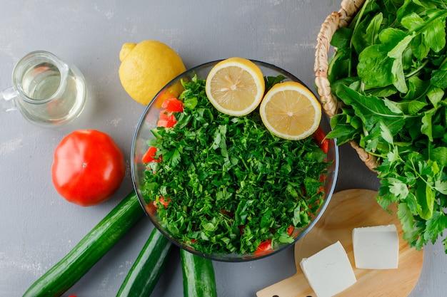 Conjunto de tomates, queso, limón, pepino y verduras picadas en un recipiente de vidrio sobre una superficie gris