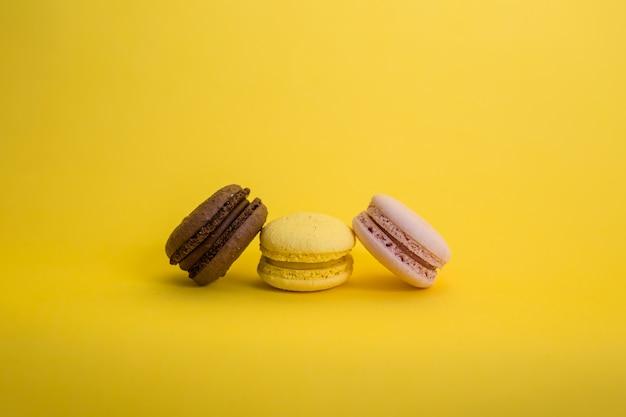 Conjunto de tres macarons en un espacio amarillo con espacio de copia. los macarrones marrones, amarillos y rosados están en una fila.