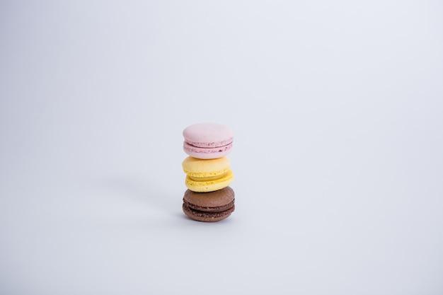 Conjunto de tres macarons en el espacio en blanco con espacio de copia. los macarrones marrones, amarillos y rosados están en una fila.