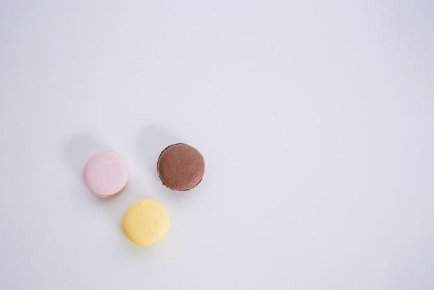 Un conjunto de tres macarrones en un espacio en blanco con una copia del espacio. los macarrones marrones, amarillos y rosados se encuentran en un círculo.