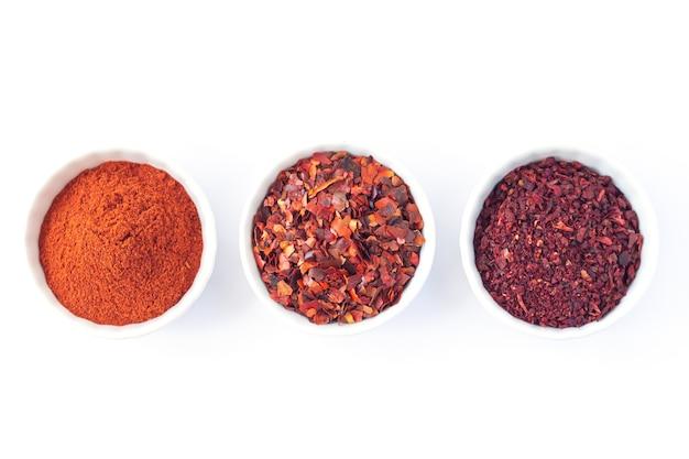 Conjunto de tres tazones con especias rojas aisladas sobre fondo blanco. chile, pimienta en polvo, tomates secos vista superior