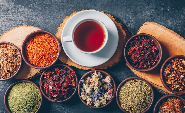 Conjunto de trozos de madera y una taza de té y hierbas de té en cuencos sobre un fondo oscuro con textura. aplanada