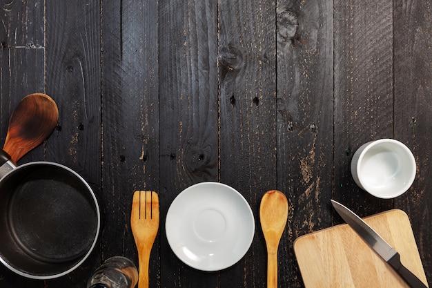 Conjunto de utensilios de cocina en el fondo de madera negro.