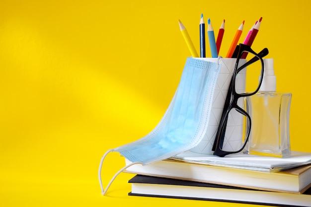 Conjunto de útiles escolares, gafas, desinfectante de manos y máscara protectora médica.