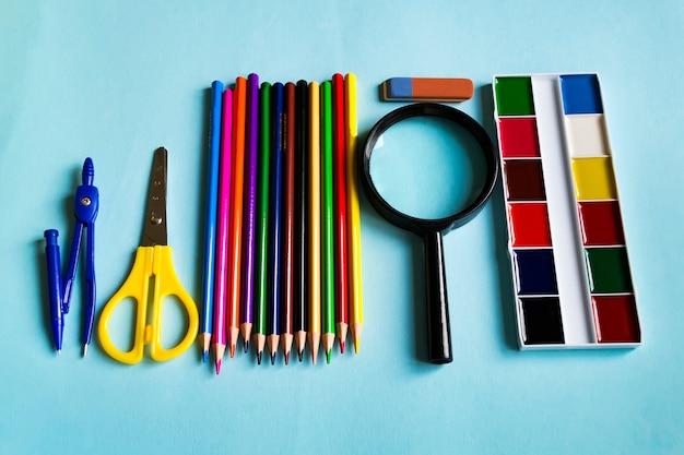 Un conjunto de útiles escolares. lupa, lápices, regla, vaina, acuarela sobre papel azul.