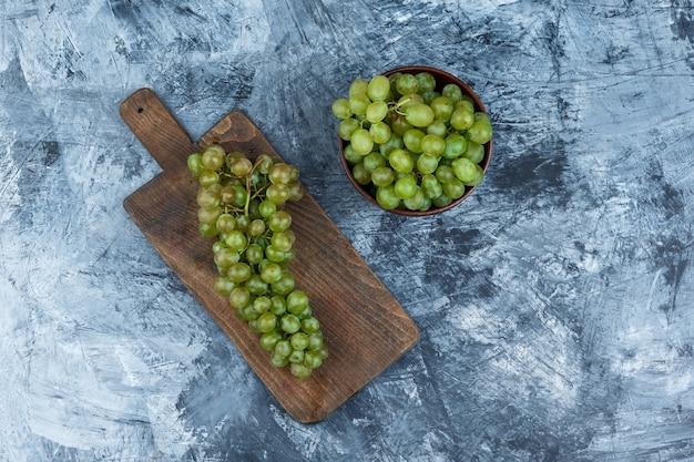 Conjunto de uvas blancas sobre tabla de cortar y uvas blancas en un recipiente sobre un fondo de mármol azul oscuro. endecha plana.