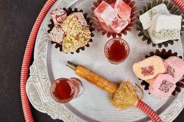 Conjunto de varias delicias turcas en un tazón en una bandeja de metal cerca del tubo de cachimba