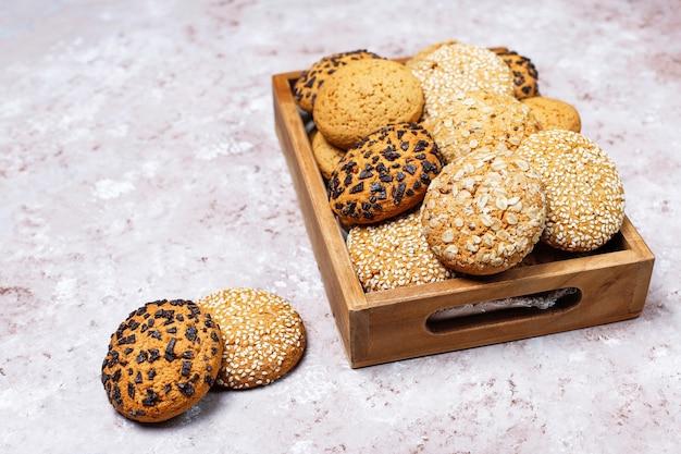 Conjunto de varias galletas de estilo americano en bandeja de madera sobre fondo de hormigón ligero. galletas de mantequilla con semillas de sésamo, mantequilla de maní, avena y galletas de chispas de chocolate.