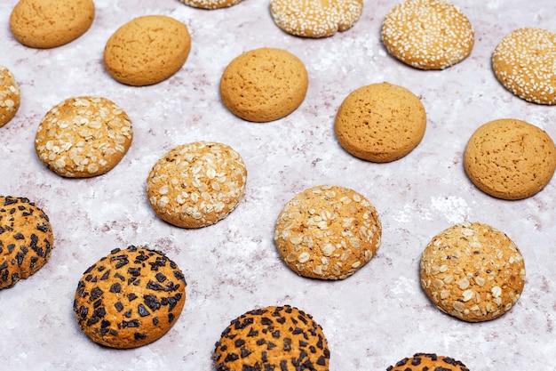 Conjunto de varias galletas de estilo americano sobre un fondo de hormigón ligero. galletas de mantequilla con confeti, semillas de sésamo, mantequilla de maní, avena y galletas de chispas de chocolate.
