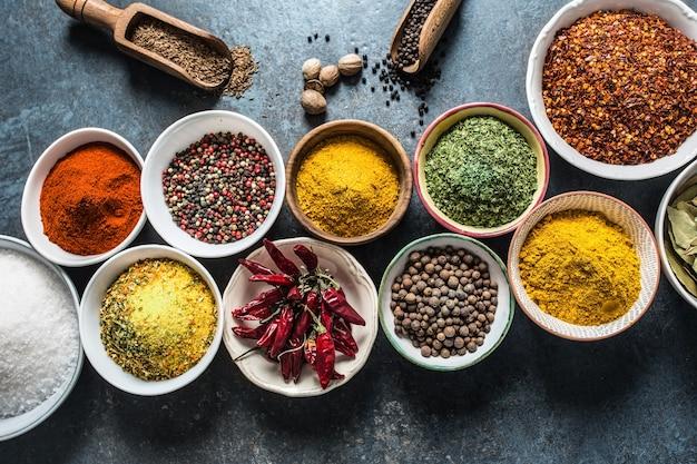 Conjunto de variedad de especias aromáticas y hierbas en tazones.