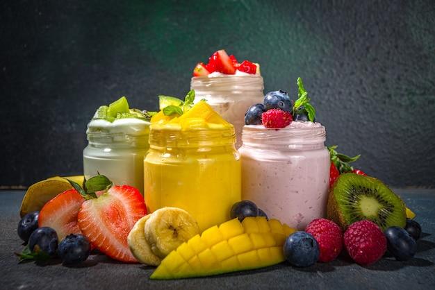 Conjunto de varios yogures dulces de frutas y bayas en frascos de vidrio. variedad de yogures de desayuno saludable con arándano, fresa, mango, kiwi, frambuesa, con frutas frescas y bayas, fondo oscuro