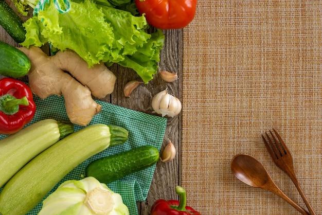 Conjunto de verduras sobre la mesa con un tenedor y una cuchara de madera.