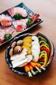 El conjunto de verduras yakiniku (carne a la parrilla) incluye zanahoria, pimiento en rodajas, cebolla en rodajas, calabaza en rodajas, eryngii y hongo shitake en un tazón de piedra con carnes wagyu a5 en rodajas.