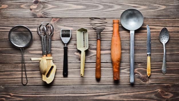 Un conjunto de viejos utensilios de cocina y cubiertos en una mesa de madera. vintage cocinando en la cocina. vista superior.
