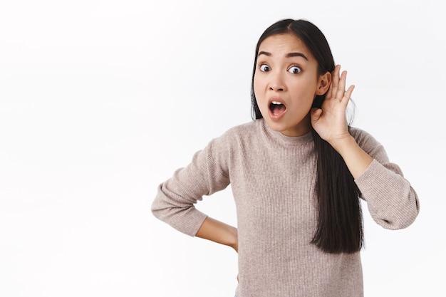 Conmocionada, abrumada, niña del este de asia reacciona de forma exagerada al oír un rumor, se toma de la mano cerca de la oreja para escuchar a escondidas, jadeando y con la mandíbula asombrada, chismorreando con un amigo sobre sus compañeros de trabajo, de pie en una pared blanca