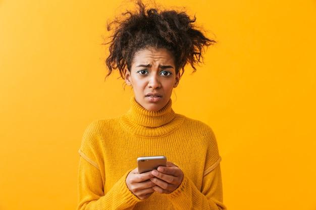 Conmocionada confundida mujer africana vistiendo suéter que se encuentran aisladas, sosteniendo el teléfono móvil