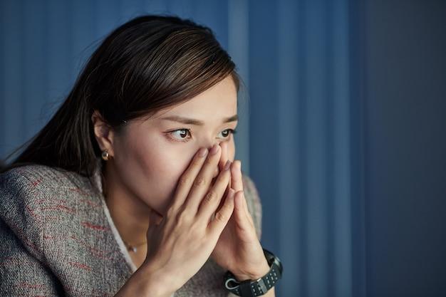 Conmocionada estresada joven empresaria asiática leyendo un correo electrónico con malas noticias en la pantalla brillante de la computadora