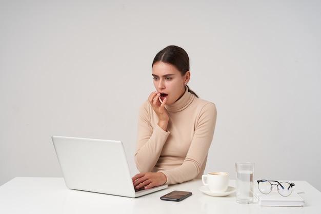 Conmocionada joven y atractiva dama de cabello oscuro levantando la mano a la boca mientras mira asombrado a la pantalla de su computadora portátil, sosteniendo la mano en el teclado, aislado sobre una pared blanca