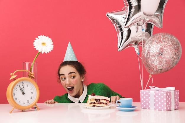 Conmocionada joven estudiante nerd celebrando su cumpleaños y mirando el pastel sobre la mesa