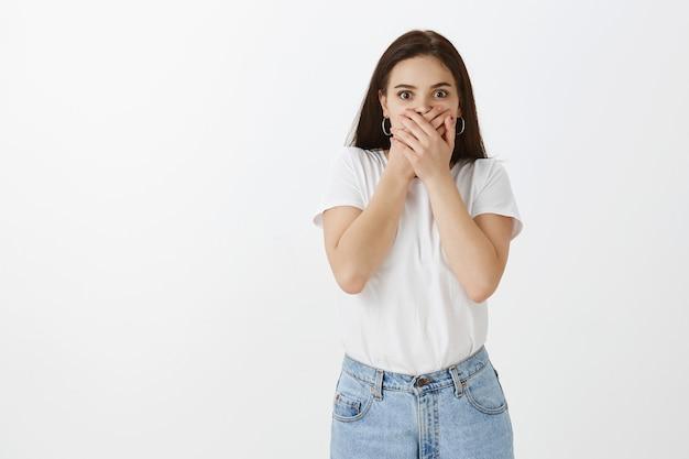Conmocionada joven posando contra la pared blanca