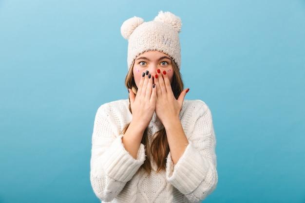 Conmocionada joven vistiendo ropa de invierno que se encuentran aisladas, cubren la cara