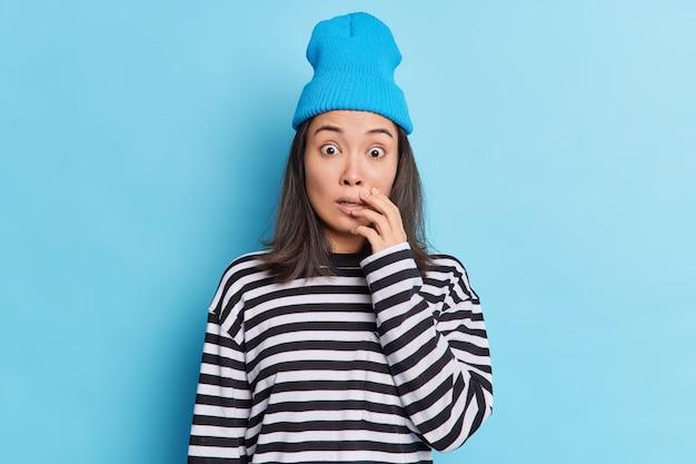 Conmocionada morena mujer asiática mira fijamente a la cámara, los ojos con errores tiene expresión de miedo, miedo a algo horrible
