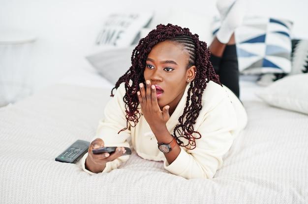 Conmocionada mujer africana con la boca abierta viendo la televisión en casa y sosteniendo un control remoto en la cama