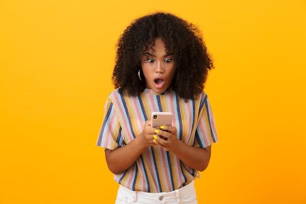 Conmocionada mujer africana emocional posando aislada sobre espacio amarillo mediante teléfono móvil.