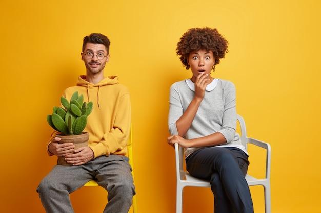 Conmocionada mujer afroamericana y hombre alegre con pose de cactus en macetas en sillas