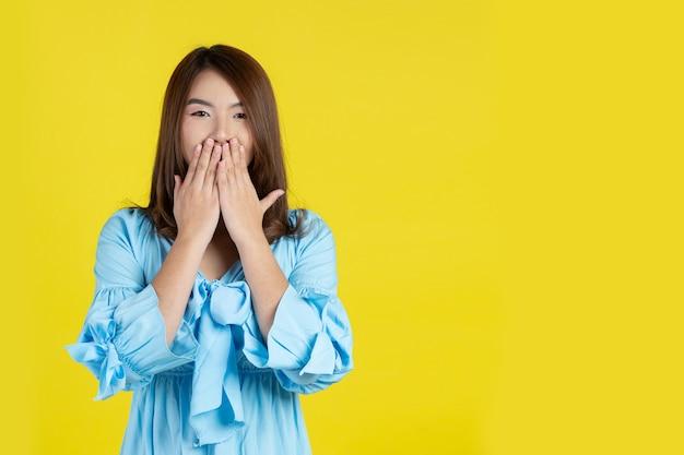 Conmocionada mujer cubriendo la boca con las manos en la pared amarilla