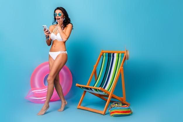 Conmocionada mujer descalza en bikini sosteniendo smartphone